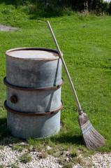 old besom leaned against barrel