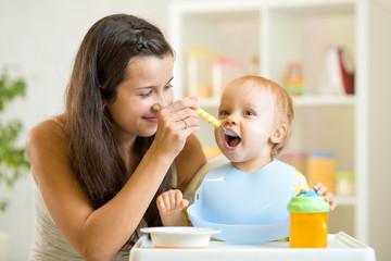 Beautiful young woman feeds child boy