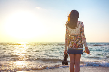 woman looking far away at the sunset on the beach Wall mural