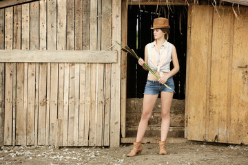 Full length portrait of young woman with hat on the farm
