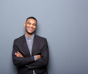 Happy young business man smiling with arms crossed