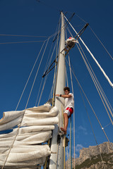 Fototapete - young man working on sailing ship