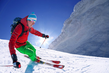 Skier skiing in high mountains against blue sky