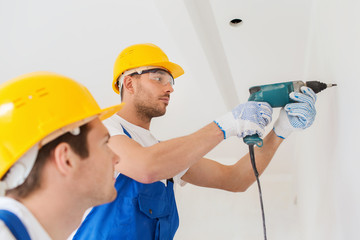group of builders with drill indoors
