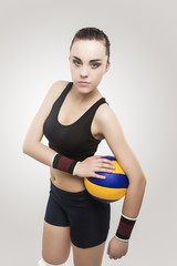 Female Volleyball Athlete in Training Outfit Poses Against Gray