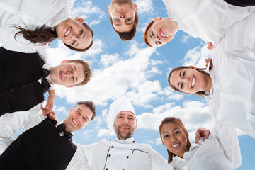 Happy Chef And Waiters Standing In Huddle Against Sky