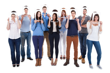 College Students Holding Photographs In Front Of Faces