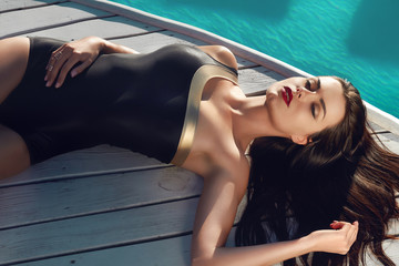 Sexy woman is sunning by swimming pool have fun at beach party