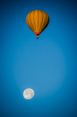 Hot air balloon flying in the blue sky with the moon