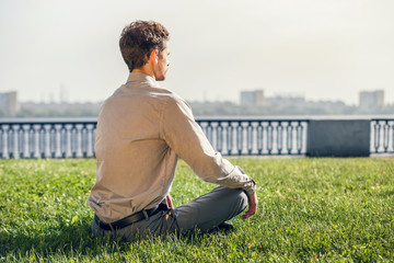 Man in office suit meditate on the green lawn