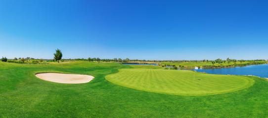 Foto auf Acrylglas Golf Panorama golf course lush grass. On the lake.