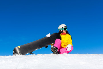snowboarder woman sitting on snow mountain slope
