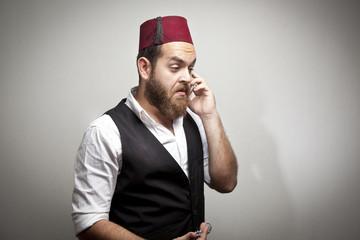 Man in traditional turkish hat and dress kabadayi talking phone