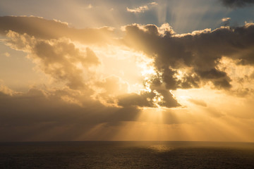 Dramatic sunset rays through a cloudy dark sky over the ocean