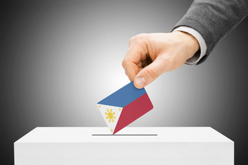 Male inserting flag into ballot box - Philippines