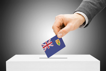 Male inserting flag into ballot box - Turks and Caicos Islands