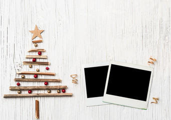 Christmas tree and instant photo on vintage wooden background