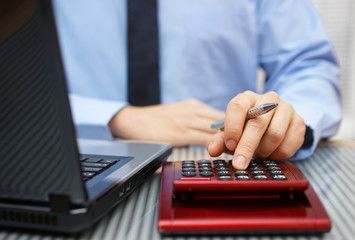 Closeup of businessman working on calculator and laptop