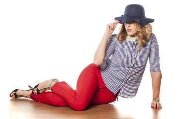young woman in red trousers and hat posing on a white background