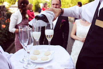 Waiter serving champagne on a tray wedding