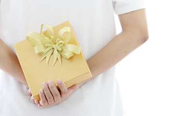 woman hiding gold gift box