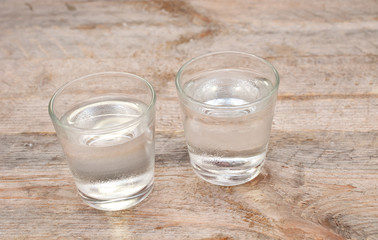 Two glasses of vodka on wooden table
