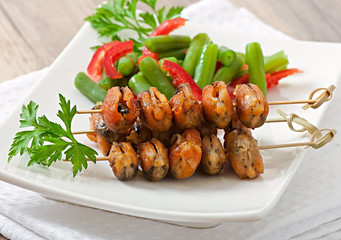 Fried mussels with onions on skewers c garnish of green beans an