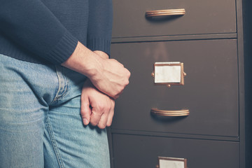 Man standing by file cabinet