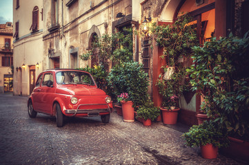 Fototapeta Old vintage cult car parked on the street by the restaurant, in