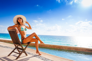 Beautiful tanned woman with sunglasses sunbathes