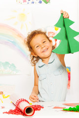 Positive girl holds carton Xmas tree standing