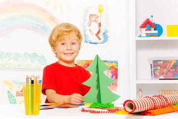 Positive cute small boy holding carton Xmas tree