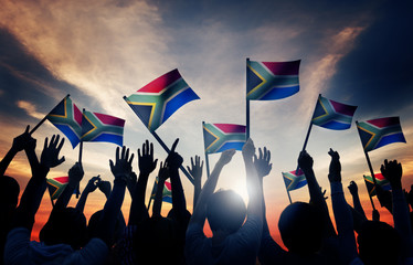 People Waving South African Flags in Back Lit
