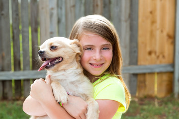 Blond kid girl with chihuahua pet dog playing