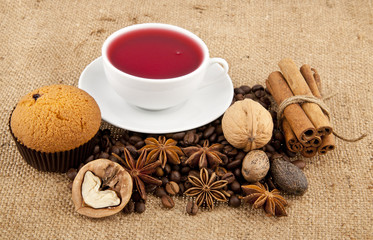 cakes, grains of coffee, seasonings and cup of floral tea