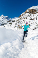Woman happy running on snow in winter