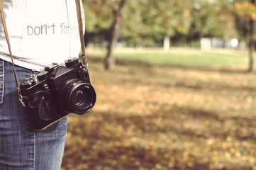 autumn photo with girl standing in a park with old camera