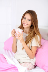 Young beautiful woman sitting in bed with cup of hot drink