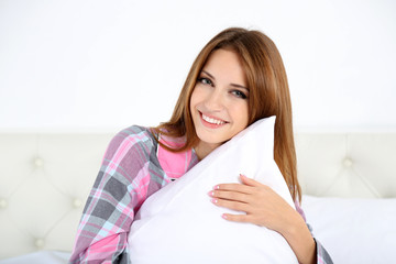 Young beautiful woman sitting on bed and holding pillow