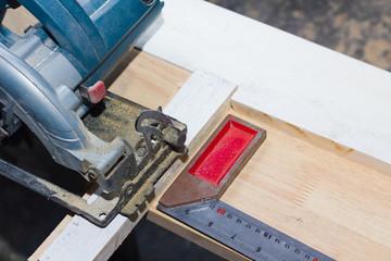circular saw cutting wood and iron ruler