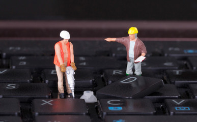 Miniature workers with drill working on keyboard