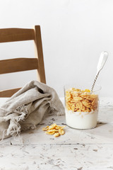 breakfast with white yogurt and corn flakes on glass with spoon
