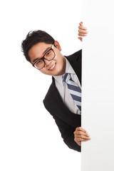 Asian businessman peeking from behind blank banner