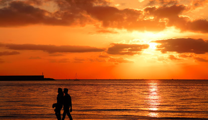 young couple walking by the sea at sunset