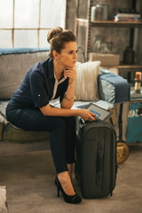 Thoughtful young woman with luggage and tablet pc