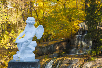 Cupid statue in autumn forest