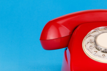 Red telephone hanging on blue background.