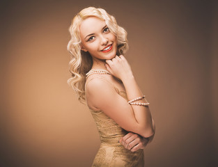 Vintage portrait of a girl in a gold dress. Blonde in studio.