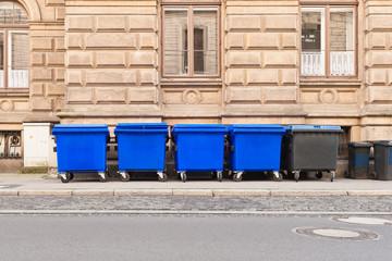 Grosse fahrbare Müllcontainer stehen aufgereiht am Strassenrand