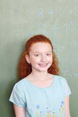 Mädchen steht vor Tafel in Schule